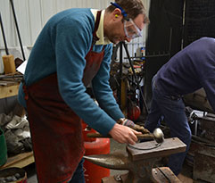 Anthony Dickens in the forge making a part for the globe cage light